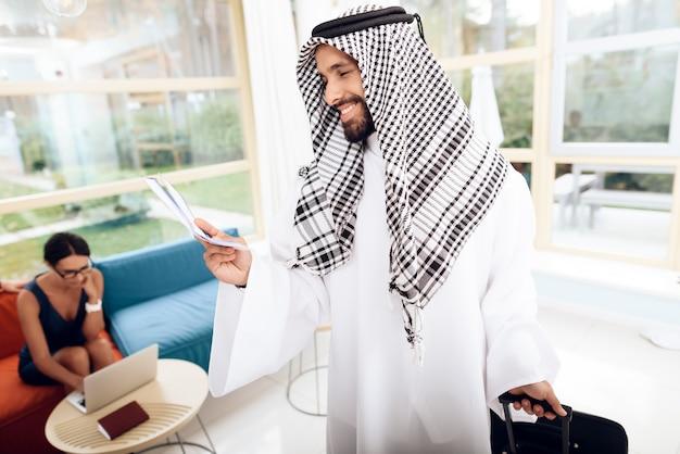 Een man in arabische kleding houdt een koffer.