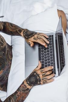 Een man in bed werkt op een laptop, post controleren, een film kijken, naar muziek luisteren