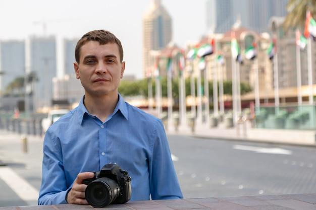 Een man in blauwe kleren houdt een camera naar de stad