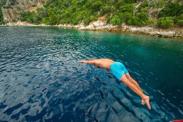 Een man in blauwe korte broek duikt van een schip in de zee bij de kust