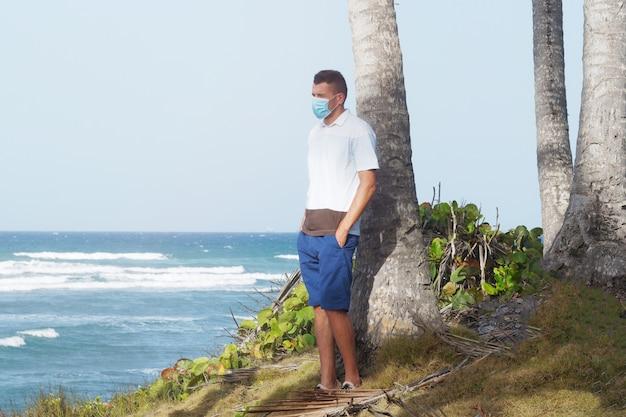 Een man in blauwe korte broek en een t-shirt met een beschermend masker kijkt naar de golven, staat op de oceaan bij een palmboom.
