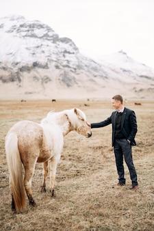 Een man in broek een trui en een jasje aait een crèmekleurig paard in het gezicht en manen tegen