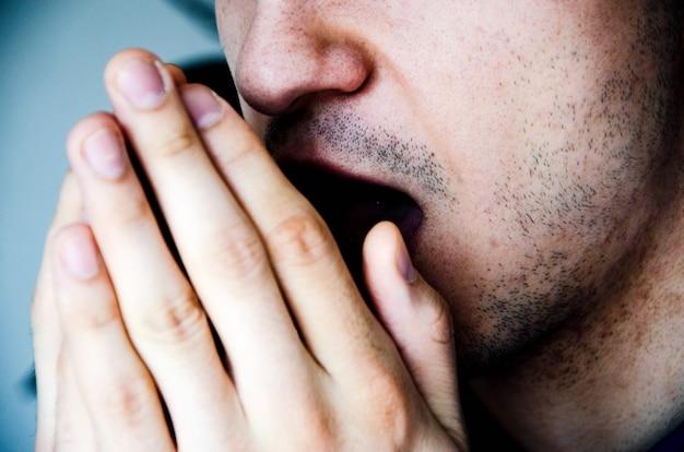 Een man in close-up hoest in zijn hand, vuist. hoesten. virusinfectie. man met stoppels. covid-19