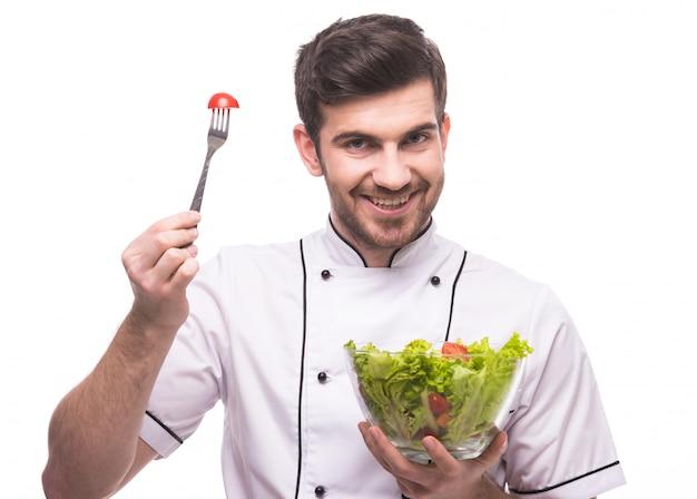 Een man in de kleding van een kok proeft een salade.