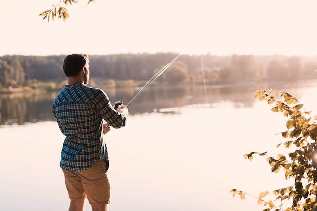 Een man in de natuur met een hengel vissen.
