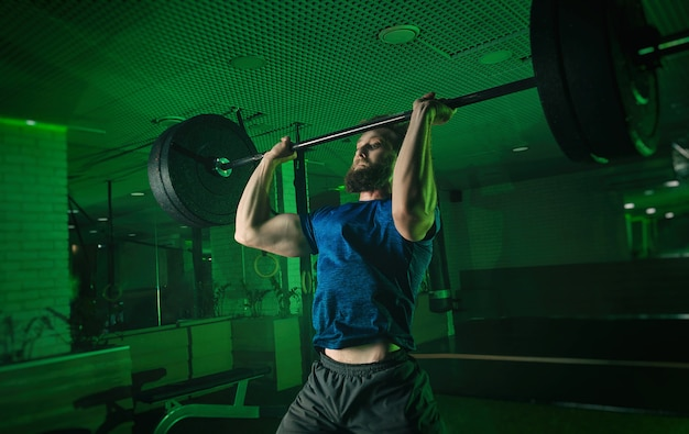 Een man in de sportschool duwt de lat