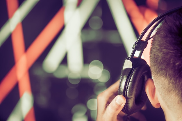 Een man in de studio koptelefoon, close-up. achteraanzicht.