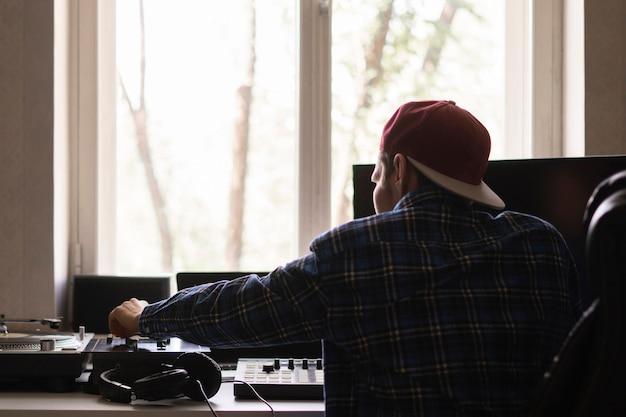 Een man in de thuismuziekstudio die een nieuw nummer maakt en geluidsproductie maakt met vintage apparatuur