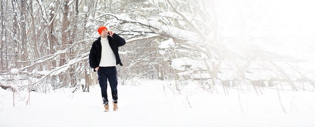 Een man in de winter in het bos. een toerist met een rugzak gaat in de winter door het bos. winterse beklimming.
