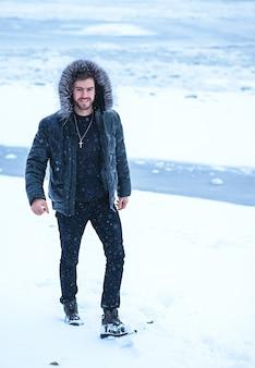 Een man in de winter op een achtergrond van sneeuw in zwarte kleding