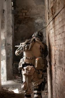 Een man in een amerikaans militair uniform in een oud verlaten gangpad beweegt met een geweer airsoft sportgam
