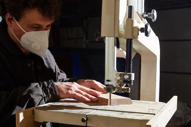 Een man in een beschermend masker snijdt een houten plank op een lintzaag
