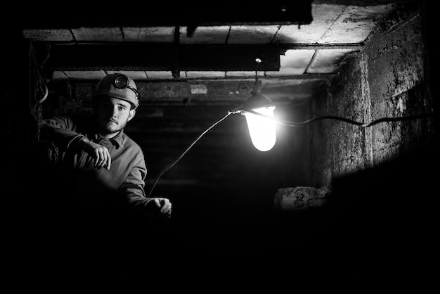 Een man in een beschermend pak en helm zit in een tunnel met een brandend plakboek. mijnwerker in de mijne