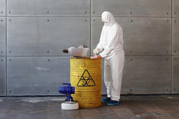 Een man in een beschermend pak en masker giet vloeistof uit een fles naast een geel vat