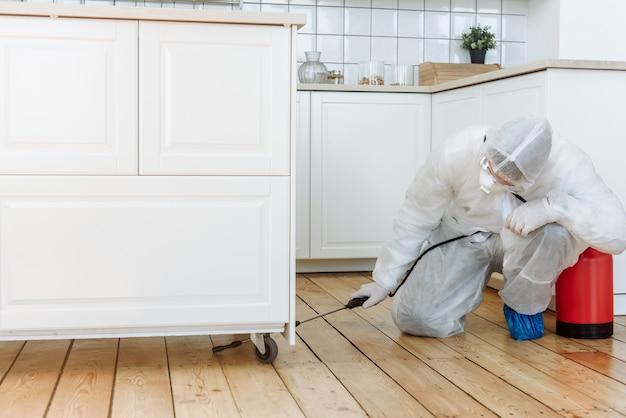 Een man in een beschermend pak met een desinfecterende spray om huishoudelijke artikelen en meubels te desinfecteren
