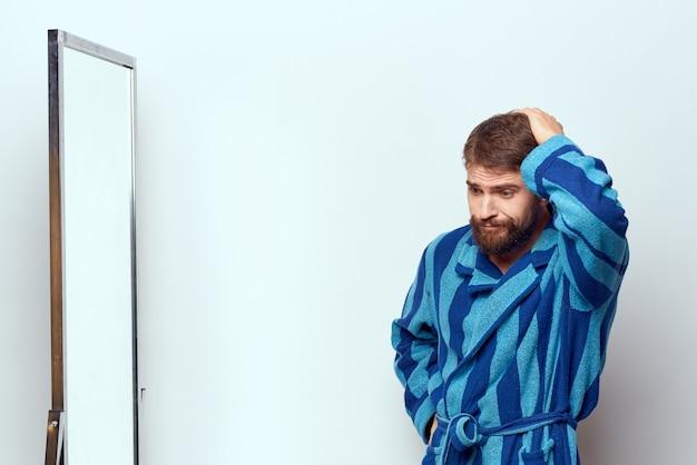 Een man in een blauw gewaad onderzoekt zichzelf in een spiegel in een lichte kamer