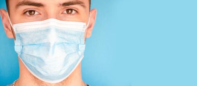 Een man in een blauw medisch masker op een blauwe achtergrond, zijwaarts. plaats voor tekst. kopieer ruimte. covid-19