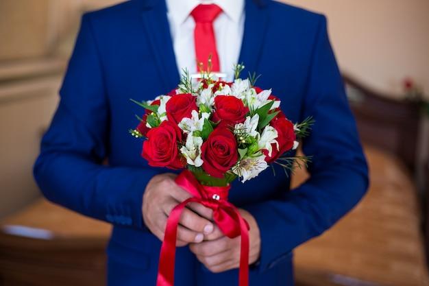 Een man in een blauw pak met een boeket rode rozen