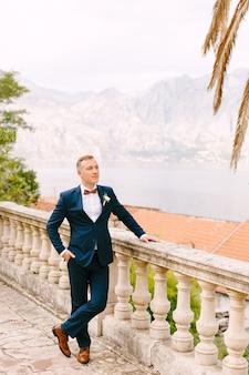 Een man in een blauw pak met een vlinderdas en een corsages staat bij de reling en kijkt naar de baai