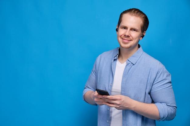 Een man in een blauw shirt gekleed draadloze koptelefoon houdt een smartphone en kijkt naar de camera. het concept van gemak van communicatie en moderne technologie.