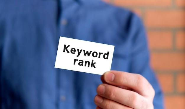 Een man in een blauw shirt houdt een bord vast met de tekst van de trefwoorden rang in één hand