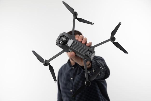 Een man in een blauw shirt met een quadcopter op een wit