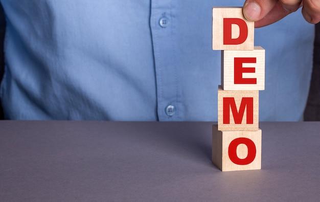 Een man in een blauw shirt stelt het woord demo verticaal samen uit houten kubussen