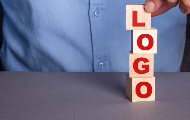 Een man in een blauw shirt stelt het woord logo verticaal samen uit houten kubussen