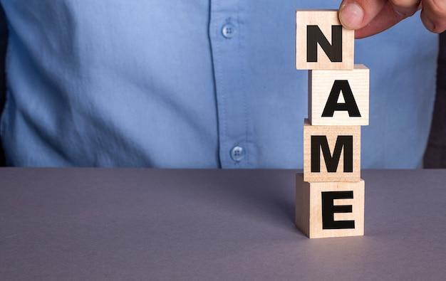 Een man in een blauw shirt stelt verticaal het woord naam samen uit houten kubussen