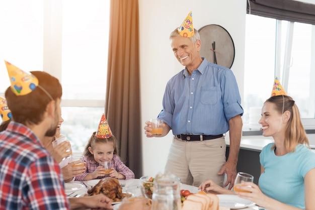Een man in een blauw t-shirt staat bij een feestelijke tafel.