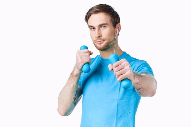 Een man in een blauwe t-shirt halters in de handen van een trainingsfitness