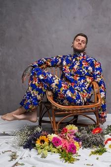 Een man in een bloemen jurk zittend op een stoel met verschillende bloemen op de vloer