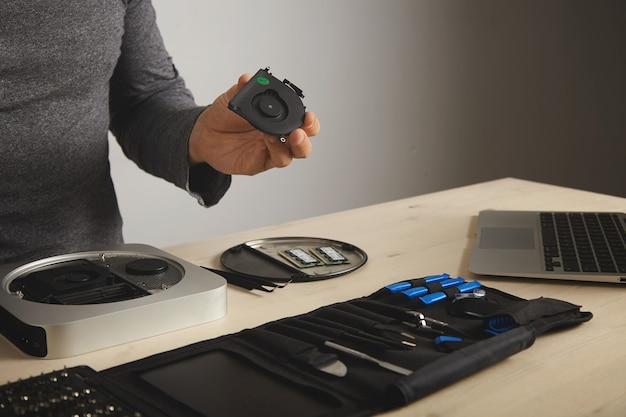 Een man in een donkergrijs t-shirt kijkt naar een koelbox die hij uit een computer heeft gehaald, zijn gereedschap voor zich op tafel