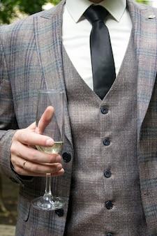 Een man in een driedelig pak houdt een glas vast om te sluiten de hand van een man houdt een glas witte wijn vast
