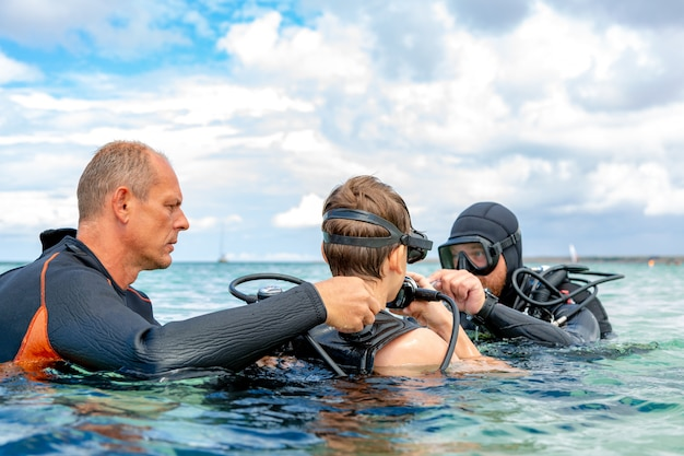 Een man in een duikpak bereidt een jongen voor om te duiken