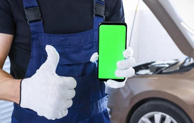 Een man in een garage houdt een smartphone met een groen scherm vast en toont een goedkeurend gebaar