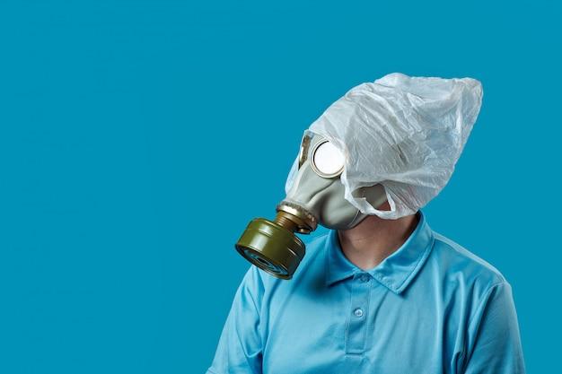 Een man in een gasmasker en een plastic zak op zijn hoofd symboliseert de bescherming van het milieu tegen vervuiling op blauw