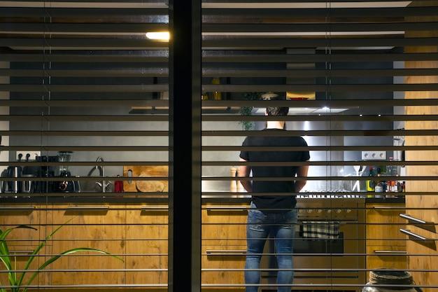 Een man in een gezellige keuken koken diner in de avond van buiten gezien door het raam, modern interieur