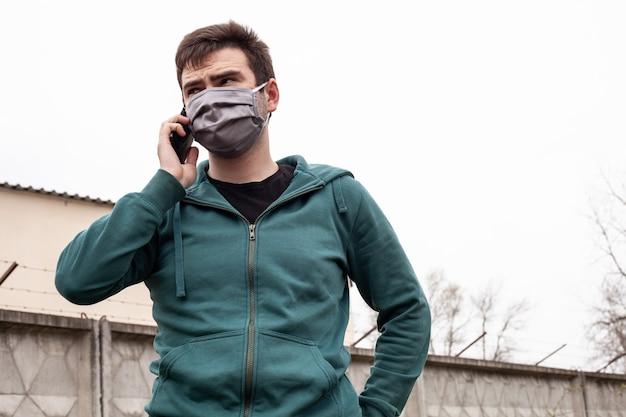Een man in een grijs medisch masker buitenshuis.