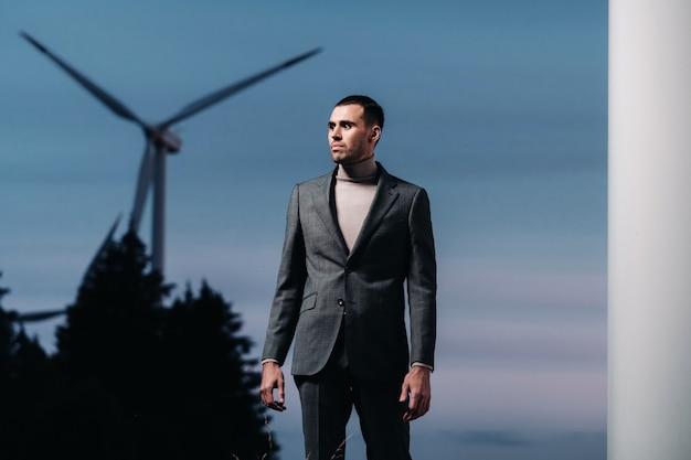 Een man in een grijs pak staat na zonsondergang naast een windmolen. zakenman in de buurt van windmolens 's nachts