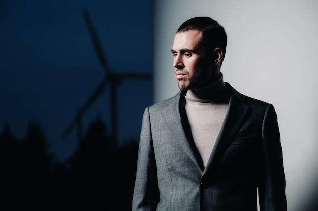 Een man in een grijs pak staat naast een windmolen na zonsondergang. zakenman in de buurt van windmolens bij nacht. modern concept van de toekomst.