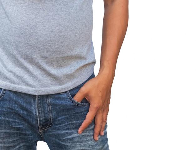 Een man in een grijs t-shirt en denims houdt zijn handen in de zakken op wit