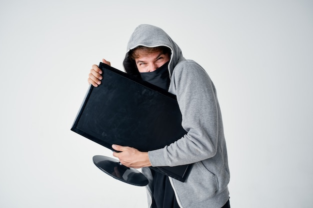 Een man in een grijze hoodie vermomt diefstaltechniek als hacker.