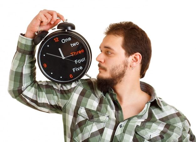 Een man in een groen shirt die naar de grote klok kijkt