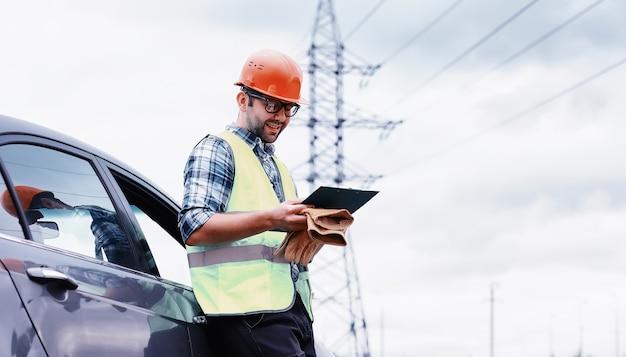 Een man in een helm en uniform, een elektricien in het veld. professionele elektricien ingenieur inspecteert hoogspanningslijnen tijdens het werk.