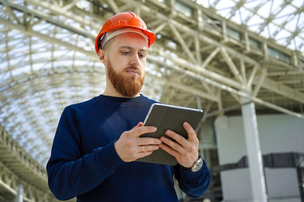 Een man in een helm in een grote ruimte met een tablet