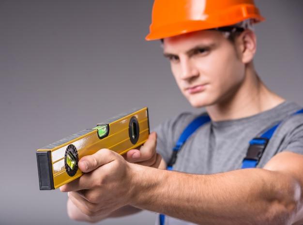 Een man in een helm met standaards en kijkt naar een centimeter.