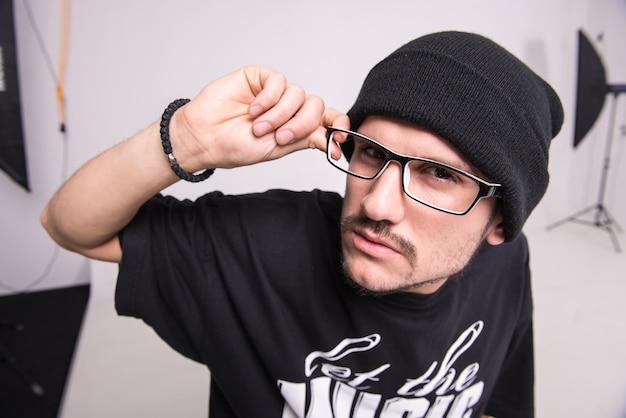 Een man in een hoed en bril kijkt naar de camera.