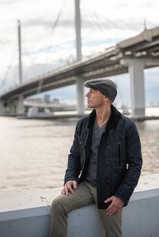 Een man in een jas en een pet op de achtergrond van de brug