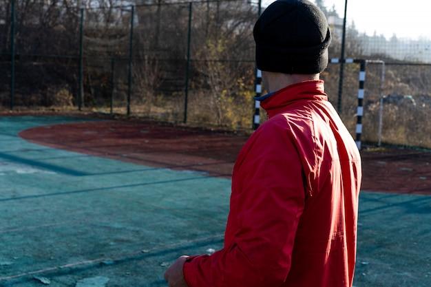 Een man in een jas en hoed kijkt naar het voetbaldoel